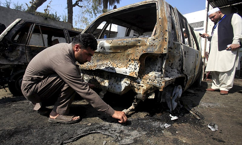 A policeman looks for evidence after a suicide attack in the courthouse of Shabqadar. ─ Reuters
