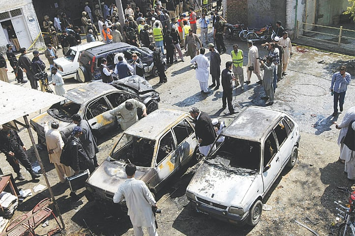 CHARSADDA: Rescue workers and security personnel gather near damaged cars to collect evidence after the suicide attack at a courts complex in Shabqadar on Monday.—White Star