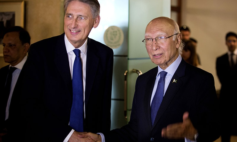 Foreign Affairs Adviser Sartaj Aziz, right, invites British Foreign Secretary Phillip Hammond for a joint news conference at the Foreign Ministry in Islamabad. ─ AP
