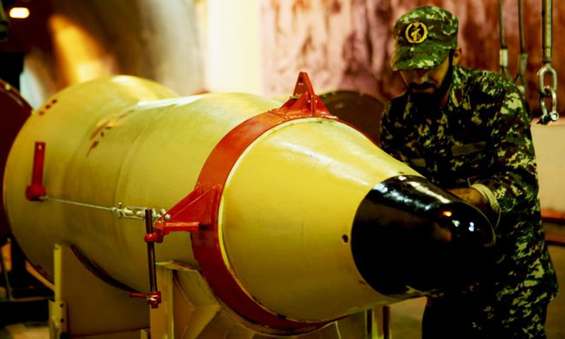 A member of the Iranian Revolutionary Guards checks a missile inside an underground depot in an undisclosed location. ─ Reuters