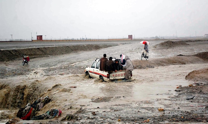 CHAMAN: A vehicle passes through a rain-affected area near the border with Afghanistan.—INP