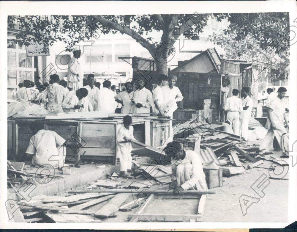 Traders gather outside their shops in Karachi after the shops were uprooted by the police for 'encroaching footpaths' the day after Ayub Khan declared Martial Law (1958).