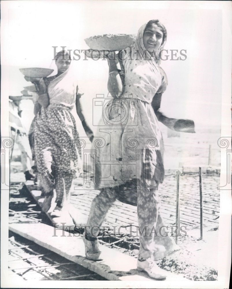 Women workers take part in the construction of a government building in Karachi in 1953.