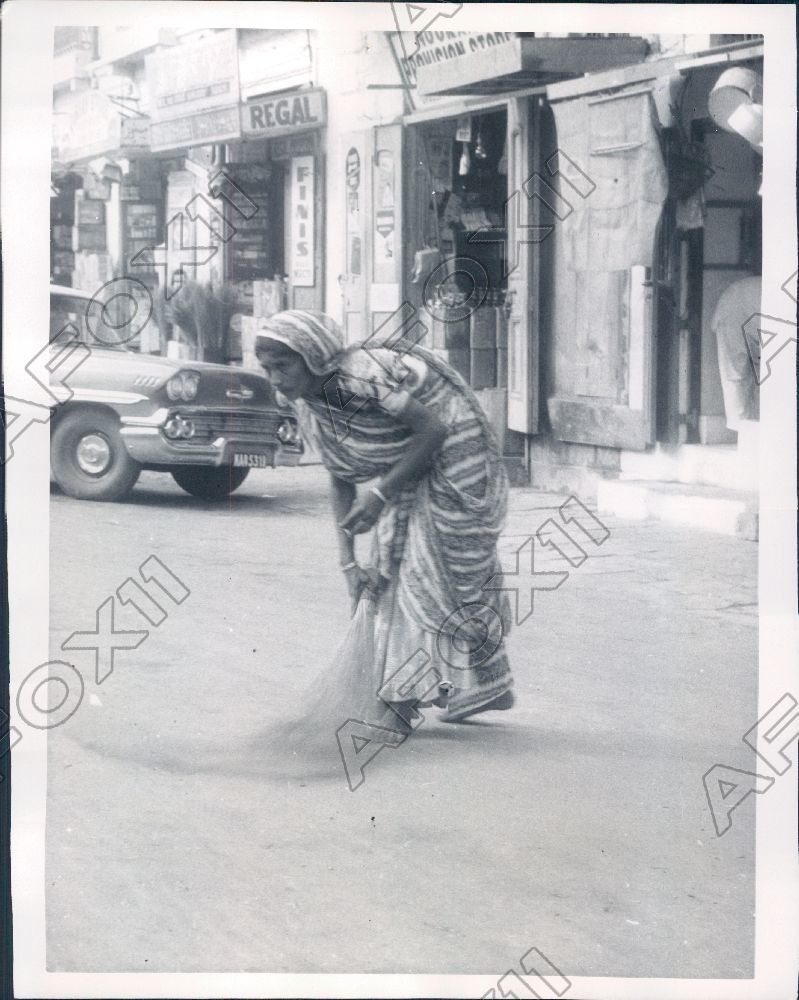 A woman worker sweeps a road in Karachi before the arrival of US President Eisenhower in 1959.