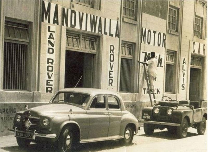 A man painting a sign over a newly opened car showroom in Karachi in 1950.