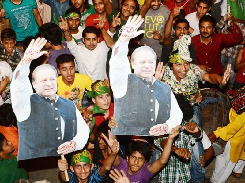 PML-N supporters hold up portraits of Nawaz Sharif to celebrate the party's victory in 2013 election.