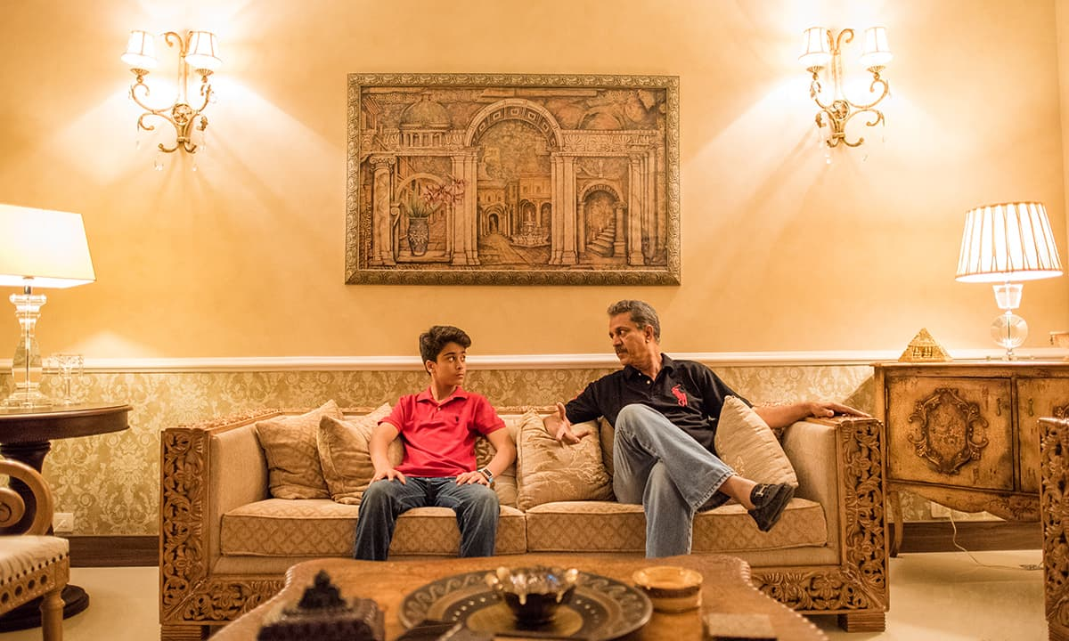 Akhtar chats with his son in their living room