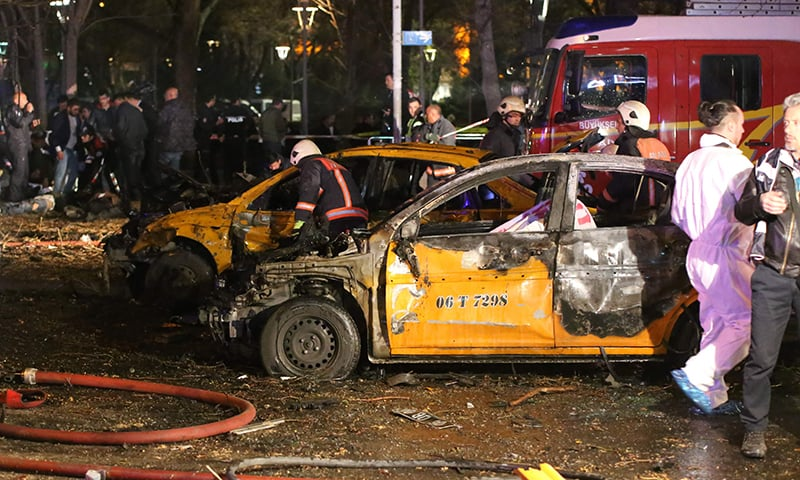Forensic police work near burnt-out vehicles at the scene of a blast in Ankara. —AFP