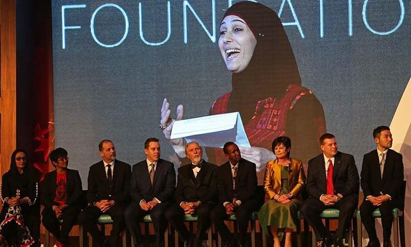 مذکورہ تصویر میں دوسری سالانہ گلوبل ٹیچر پرائز ایونٹ میں شریک شرکاء نظر آرہے ہیں جبکہ پس منظر میں انعام حاصل کرنے والی فلسطینی خاتون کا عکس دیکھا جاسکتا ہے — فوٹو; اے پی