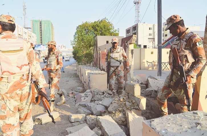 Rangers personnel inspect the checkpoint on Rashid Minhas Road near Moti Mahal, which came under an IED attack on Sunday.—White Star