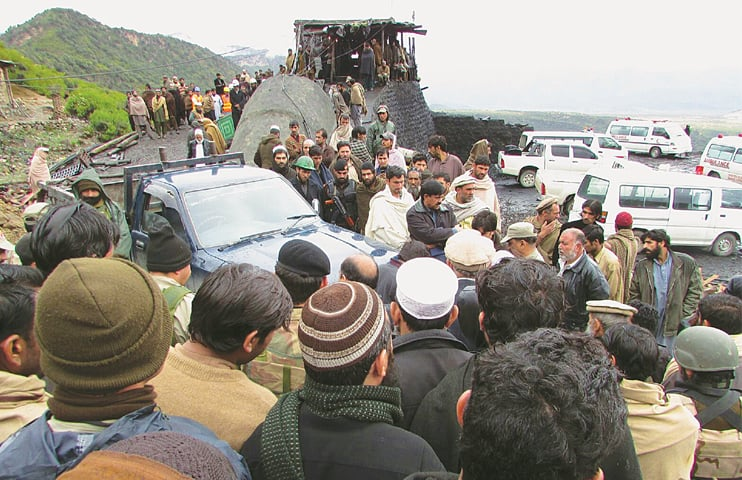 DOLI (Orakzai Agency): Security personnel and rescuers gather at the coalmine here on Sunday.—AFP