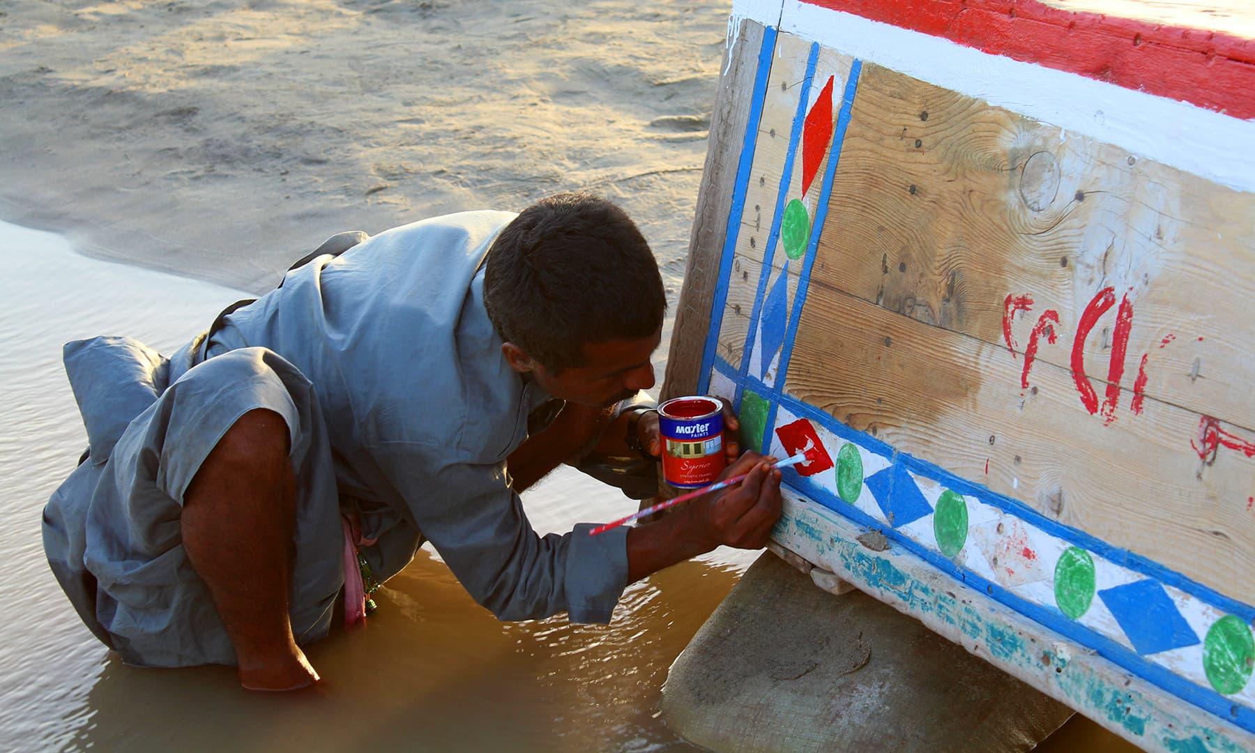 انور ملاح اپنی کشتی کو رنگ کر رہا ہے۔— فوٹو اختر حفیظ