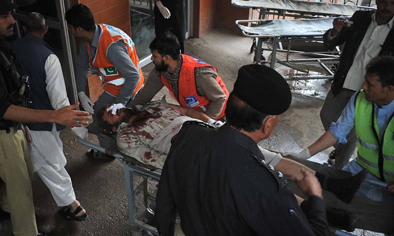 Volunteers move an injured blast victim to hospital. ─ AFP