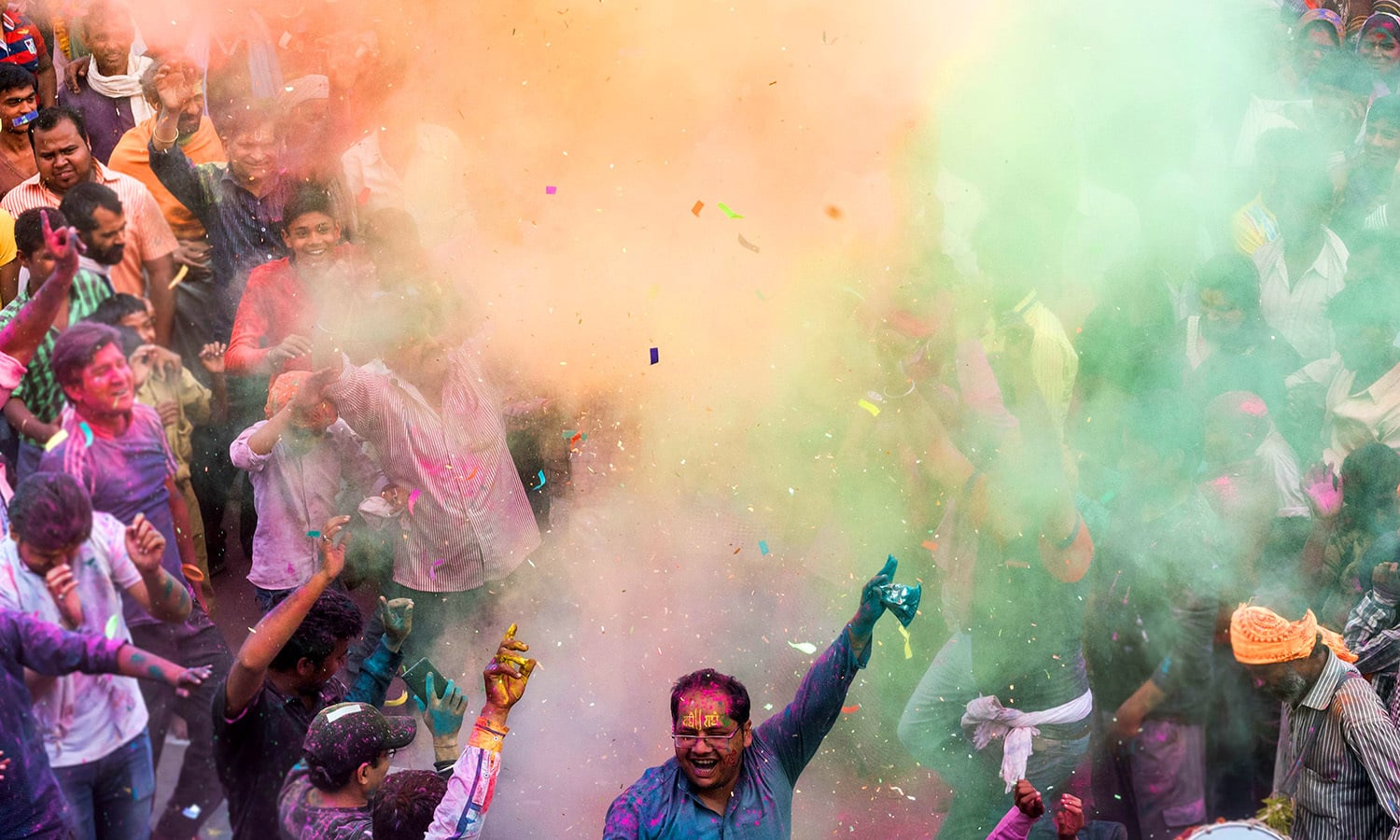 Indian villagers are covered in coloured powders during the Holi festival. ─ AFP