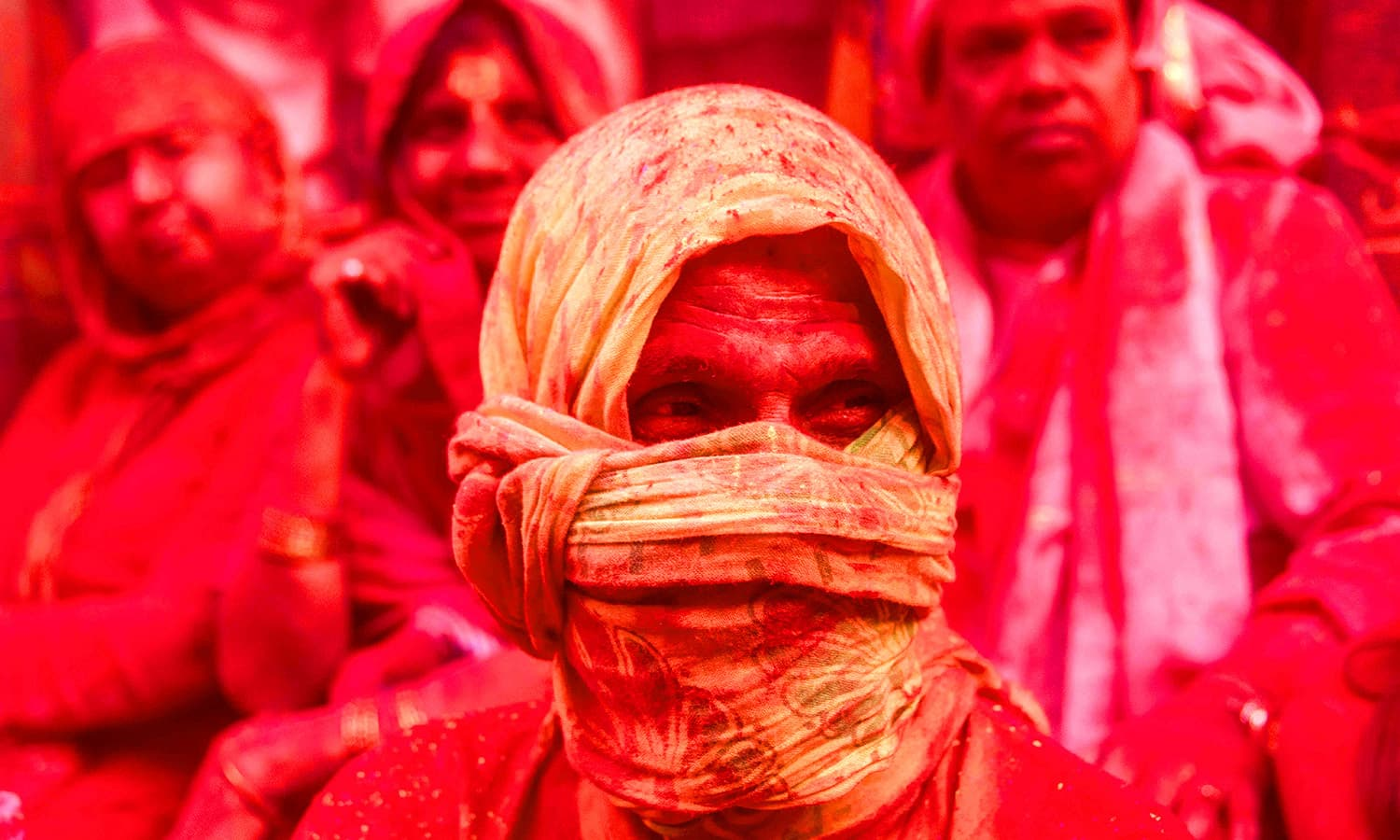 Indian villagers are covered in coloured powder during the Holi festival at the Radha Rani temple in Barsana. ─ AFP