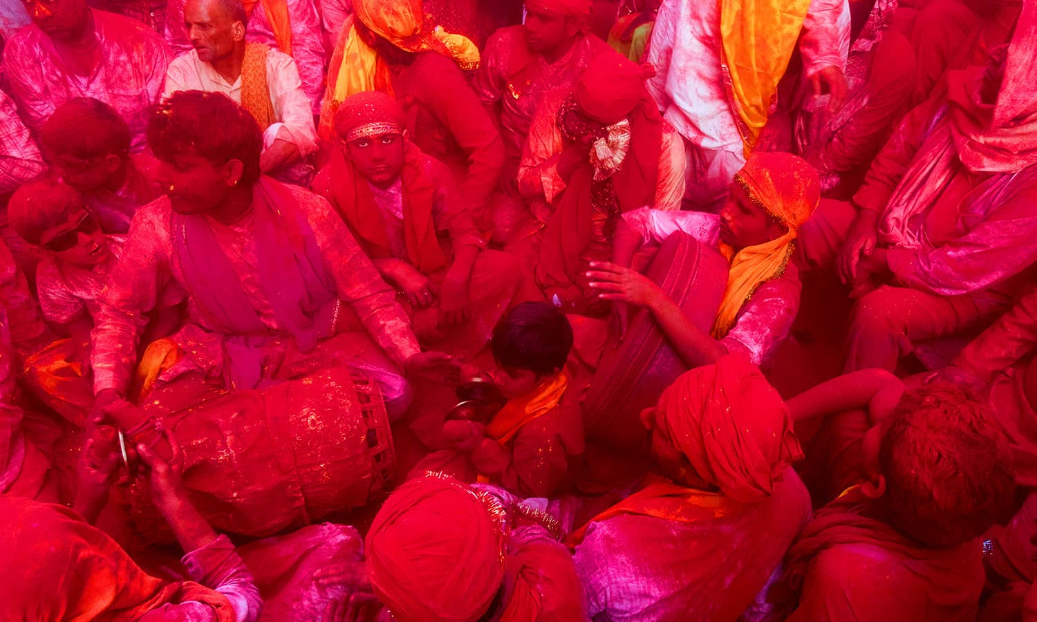 Indian villagers are covered with coloured powder during the Holi festival at the Radha Rani temple in Barsana. ─ AFP