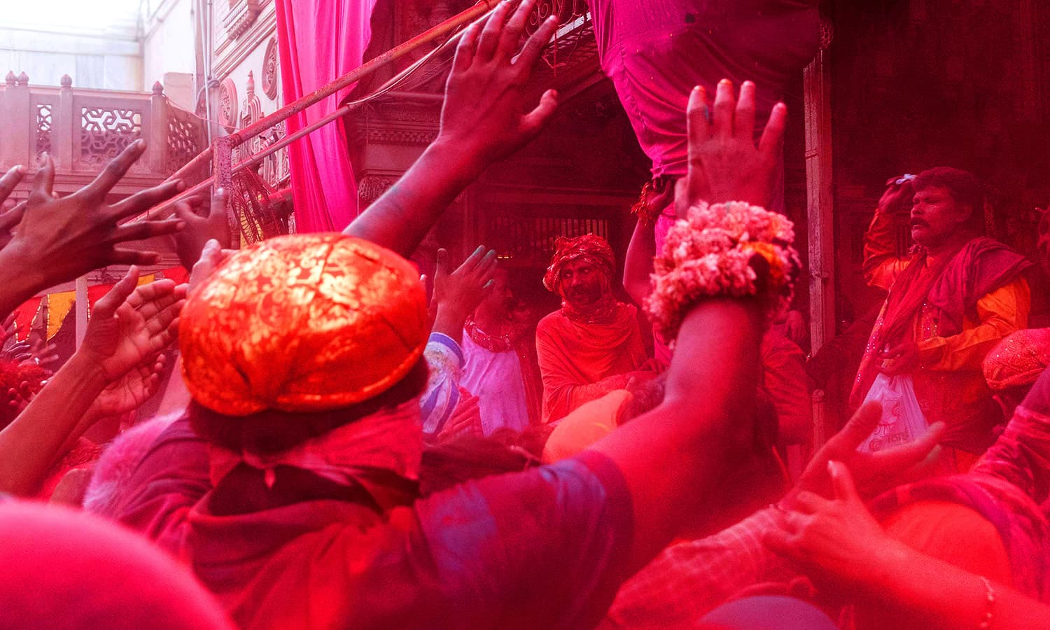 Indian villagers are covered with coloured powders during the Holi festival at the Radha Rani temple in Barsana. ─ AFP