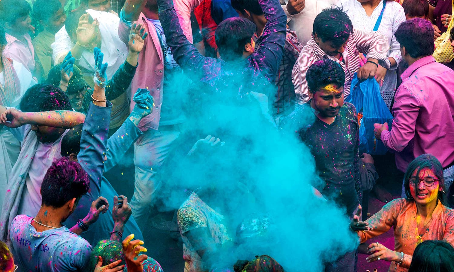 Indian villagers are covered in coloured powders during the Holi festival at the Radha Rani temple in Barsana. ─ AFP
