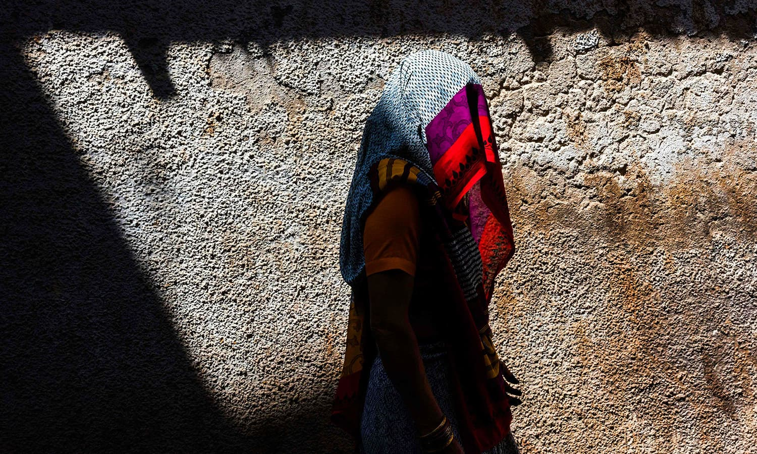 A veiled Indian woman walks on the street in Barsana. ─ AFP