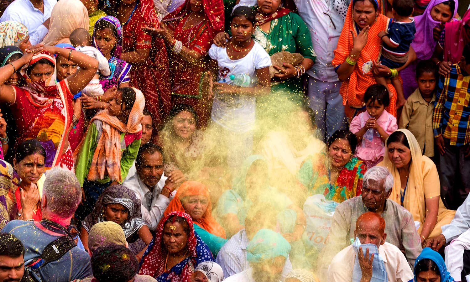 Coloured powder is thrown over Indian villagers during the Holi festival at the Radha Rani temple in Barsana. ─ AFP