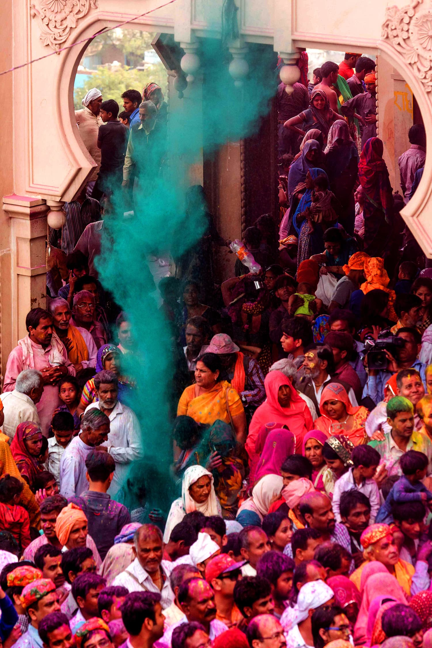 Colourful powder is thrown at Indian villagers during the Holi festival at the Radha Rani temple in Barsana. ─ AFP