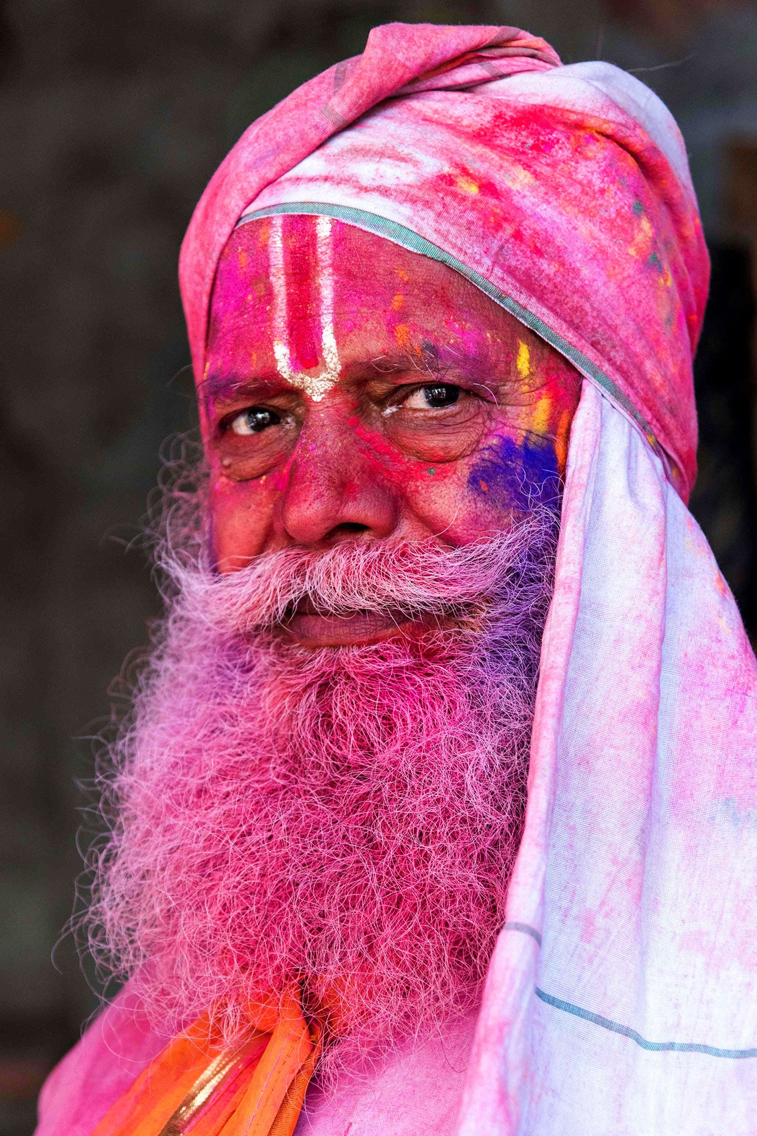 An Indian villager is smeared with colour powder during the Holi festival at the Radha Rani temple in Barsana. ─ AFP