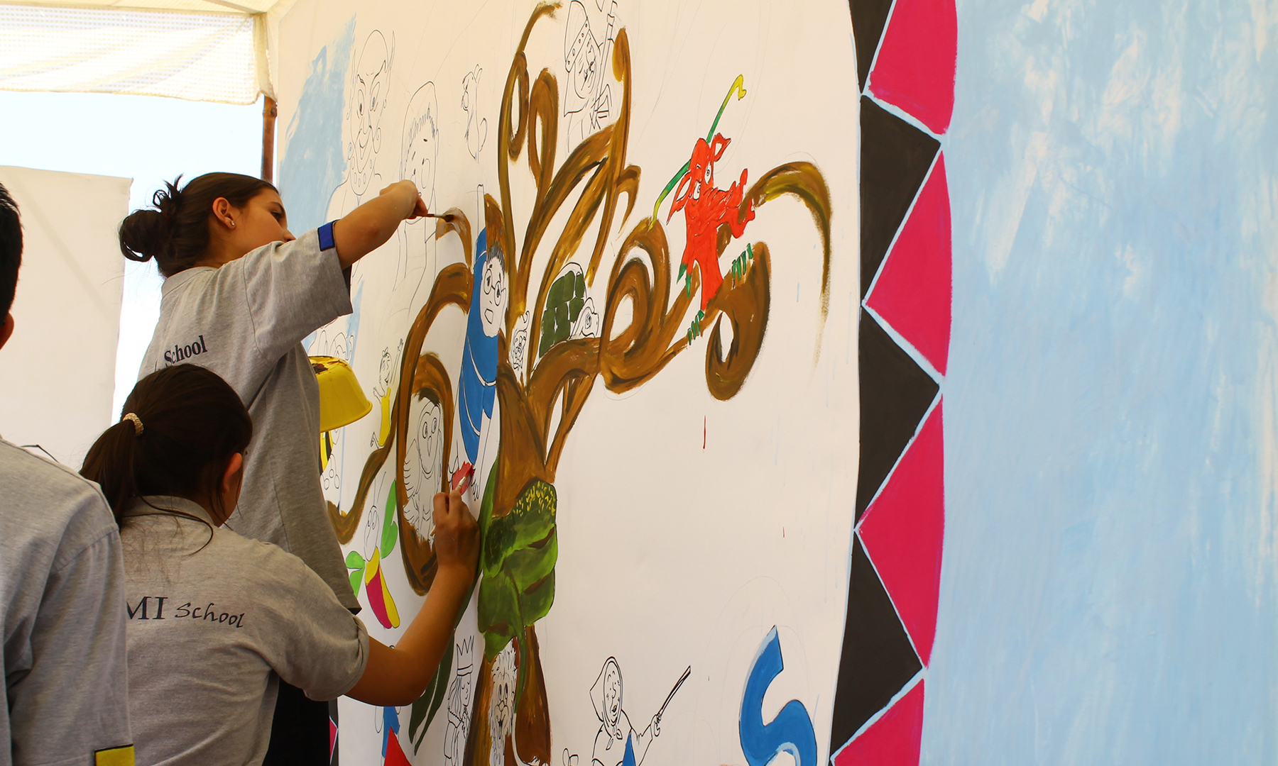 Students paint a wall mural