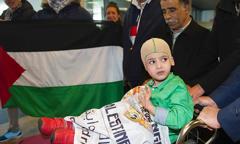 Ahmed Dawabcheh who survived a firebombing by Jewish extremists that killed his parents and brother  (C) arrives at Adolfo Suarez Airport near Madrid.─AFP