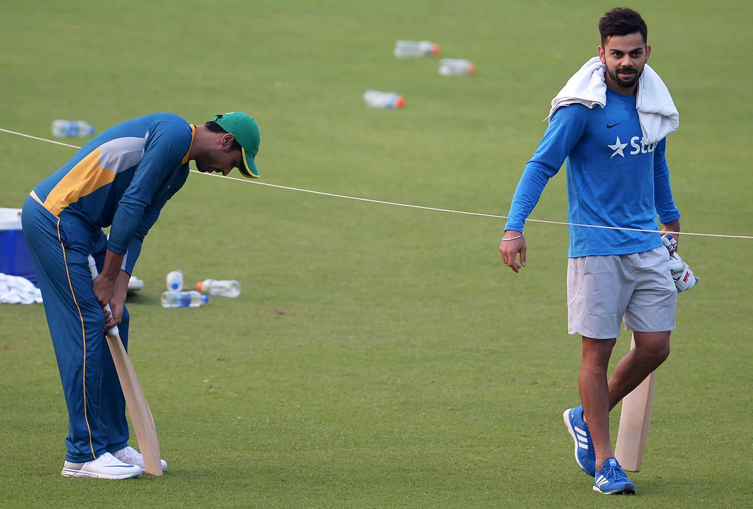 Amir checks a bat after he received it from Kohli during a training session in Kolkata. — AFP