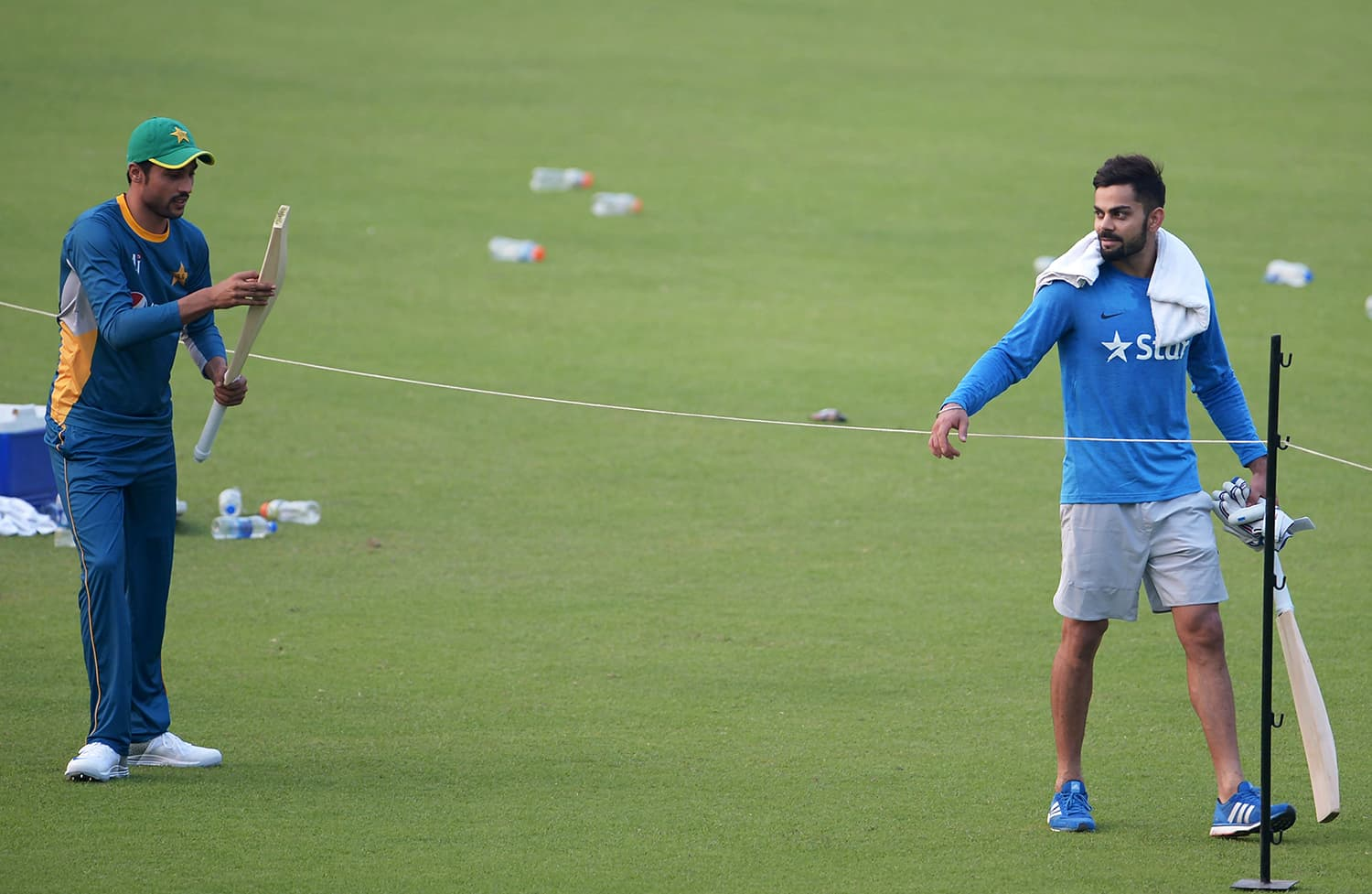 Amir checks a bat after he received it from Kohli at The Eden Gardens in Kolkata. — AFP