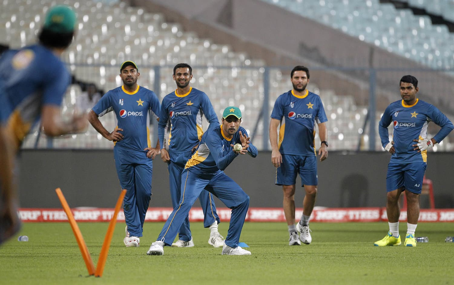 Watched by team mates, Amir practices taking catches during a training session in Kolkata. — AP