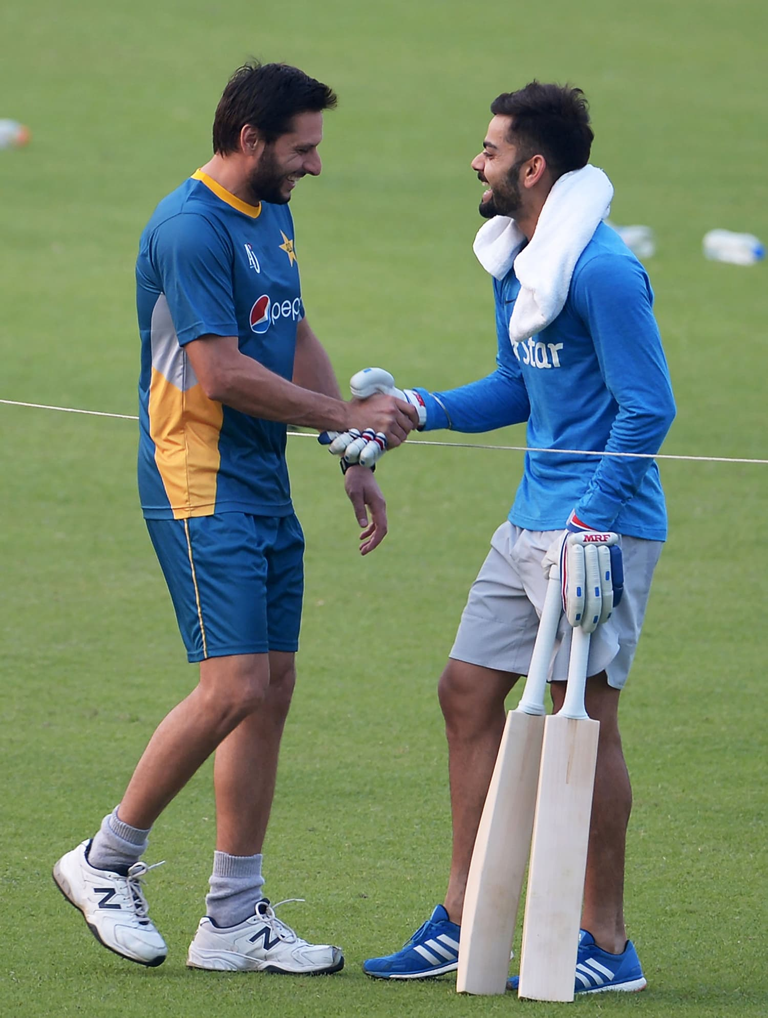 Kohli shakes hands with Afridi during a training session in Kolkata. — AFP