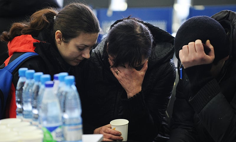 A Russian Emergency Situations Ministry employee, left, tries to comfort a relative of the plane crash victims at the Rostov-on-Don airport, about 950 kilometres south of Moscow, Russia Saturday, March 19, 2016.—AP