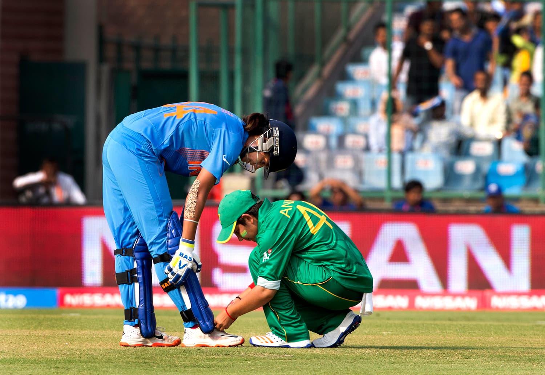 Pakistan's Anam Amin, right, ties the shoe laces of India's Harpreet Kaur. — AP