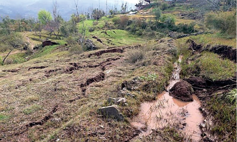 People stand near a collapsed house in Beer Garan in Murree's Sehrbagla union council. The other picture is of a swept away field in Ghoe village. — Photos by the writer