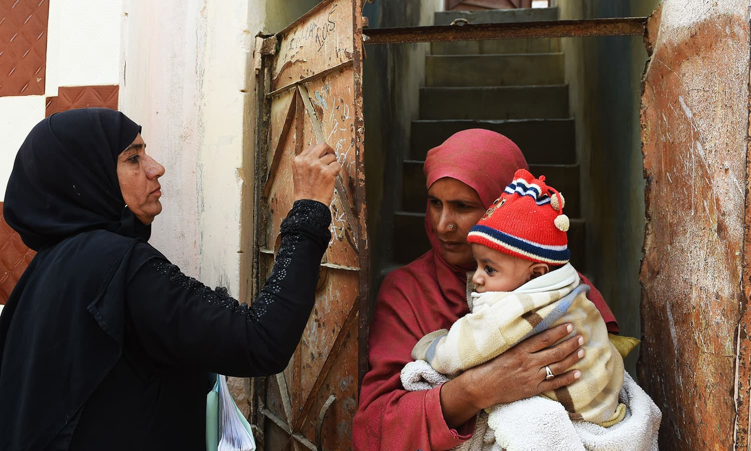 Health worker Shehnaz Ayaz (L) marks a door after administering polio drops to a child during a door-to-door polio immunisation campaign in Karachi.—AFP
