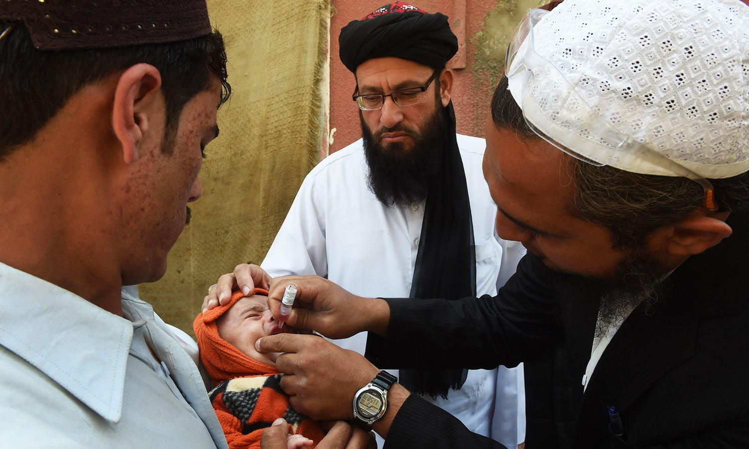 A health worker administers polio drops to a child as government appointed Islamic cleric Maulana Umar Sadiq (C) looks on during a door-to-door polio immunisation campaign in the predominantly Pashtun district of Korangi in Karachi.—AFP