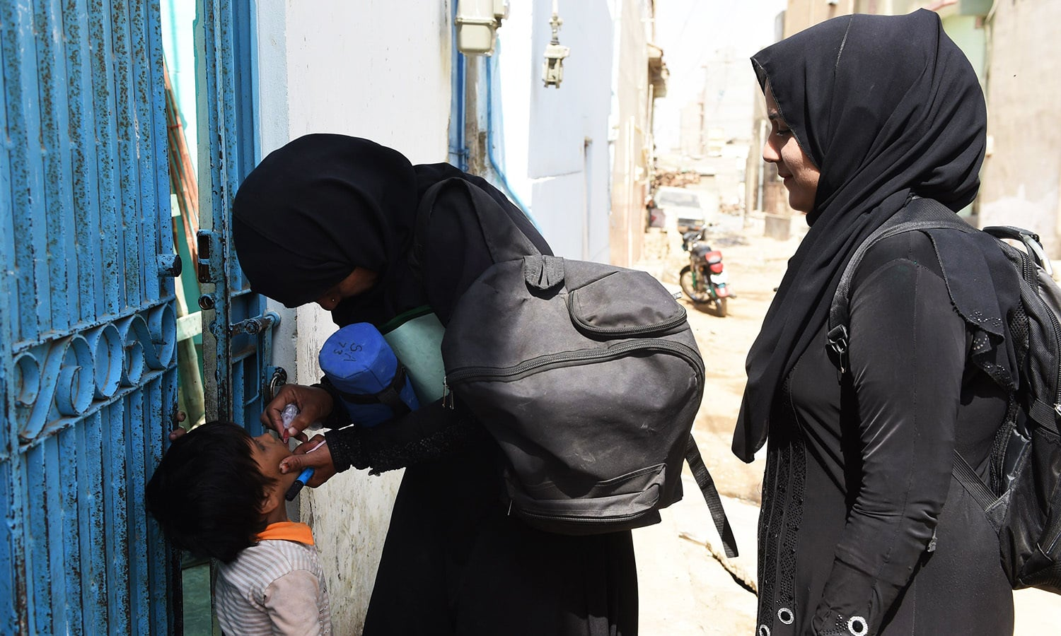 Health worker Shehnaz Ayaz (C) administers polio drops to a child during a door-to-door polio immunisation campaign in Karachi.—AFP
