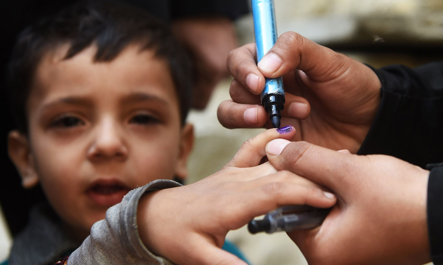 In this photograph taken on February 16, 2016, a Pakistani health worker marks a child's finger after administering polio drops outside her house during a door-to-door polio immunisation campaign in Karachi.—AFP