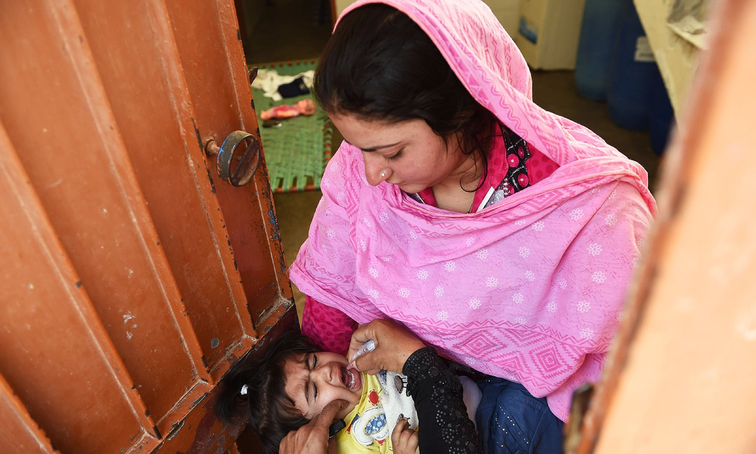 In this photograph taken on February 16, 2016, a health worker administers polio drops to a child during a door-to-door polio immunisation campaign in Karachi.—AFP