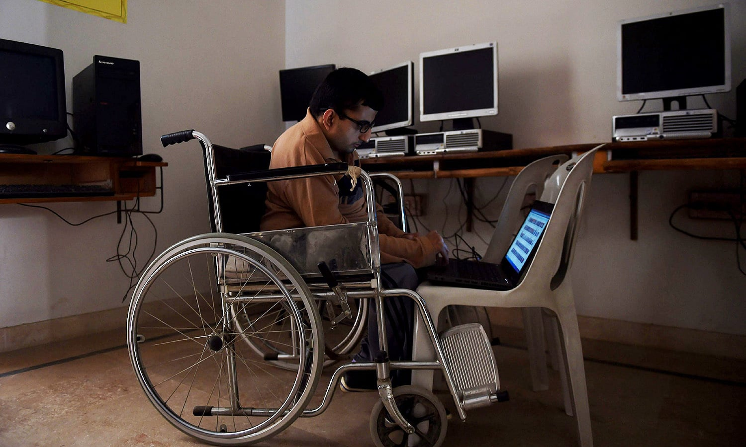 A disabled Pakistani student uses a laptop at a computer training centre in Karachi.—AFP