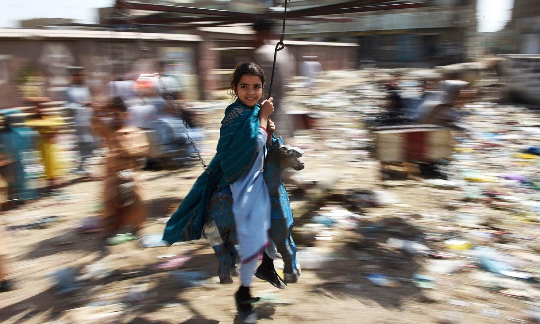 Pakistani children ride on swings in the predominantly Pashtun Korangi District of Karachi.—AFP