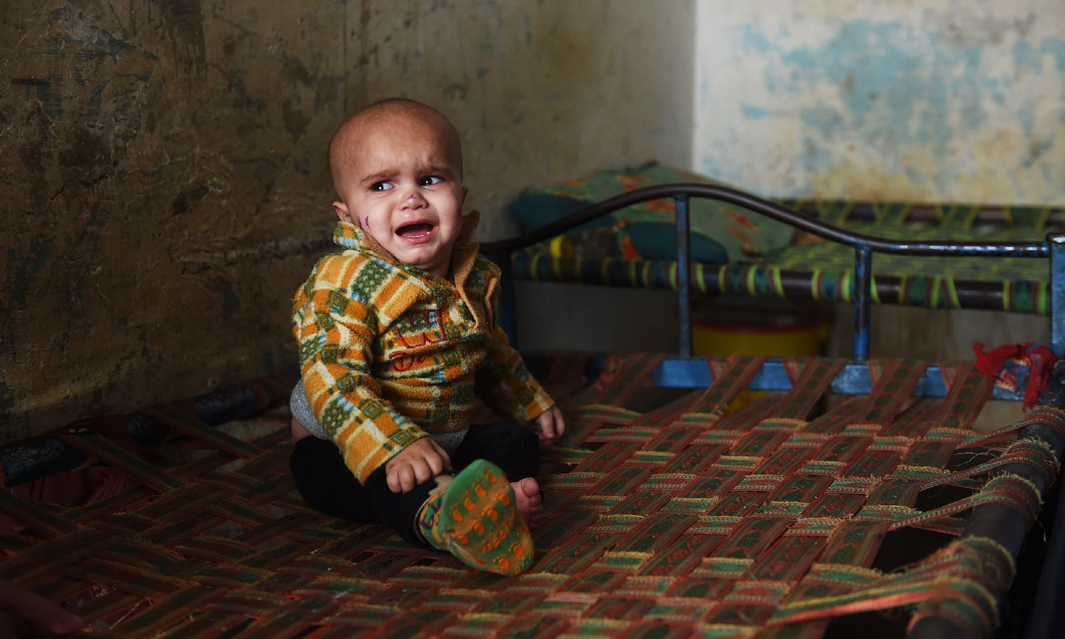 A child who is affected by polio weeps in the predominantly Pashtun Korangi District of Karachi.—AFP