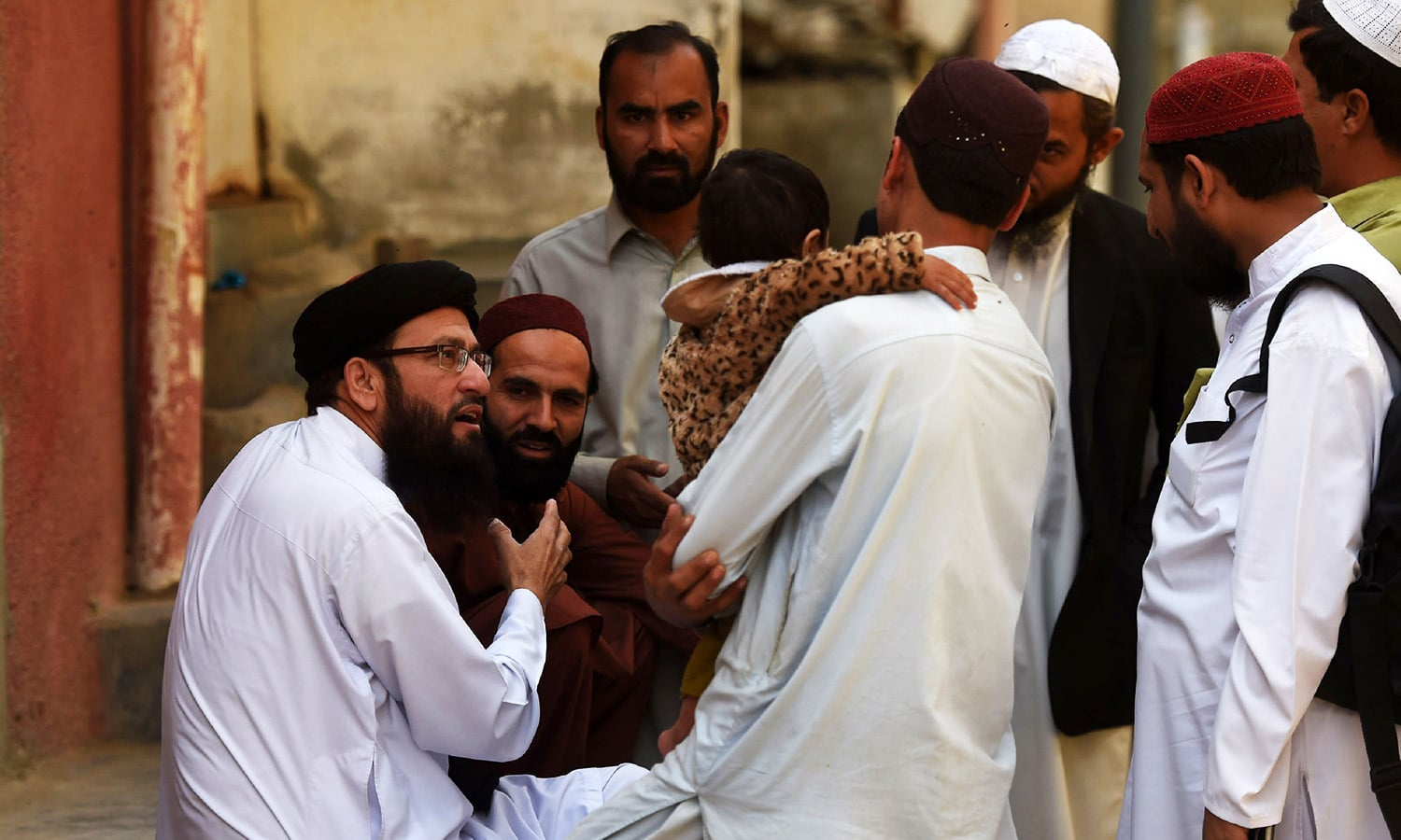 Government appointed Islamic cleric Maulana Umar Sadiq (L) explains polio vaccination programme to Pashtun community members in Karachi.—AFP