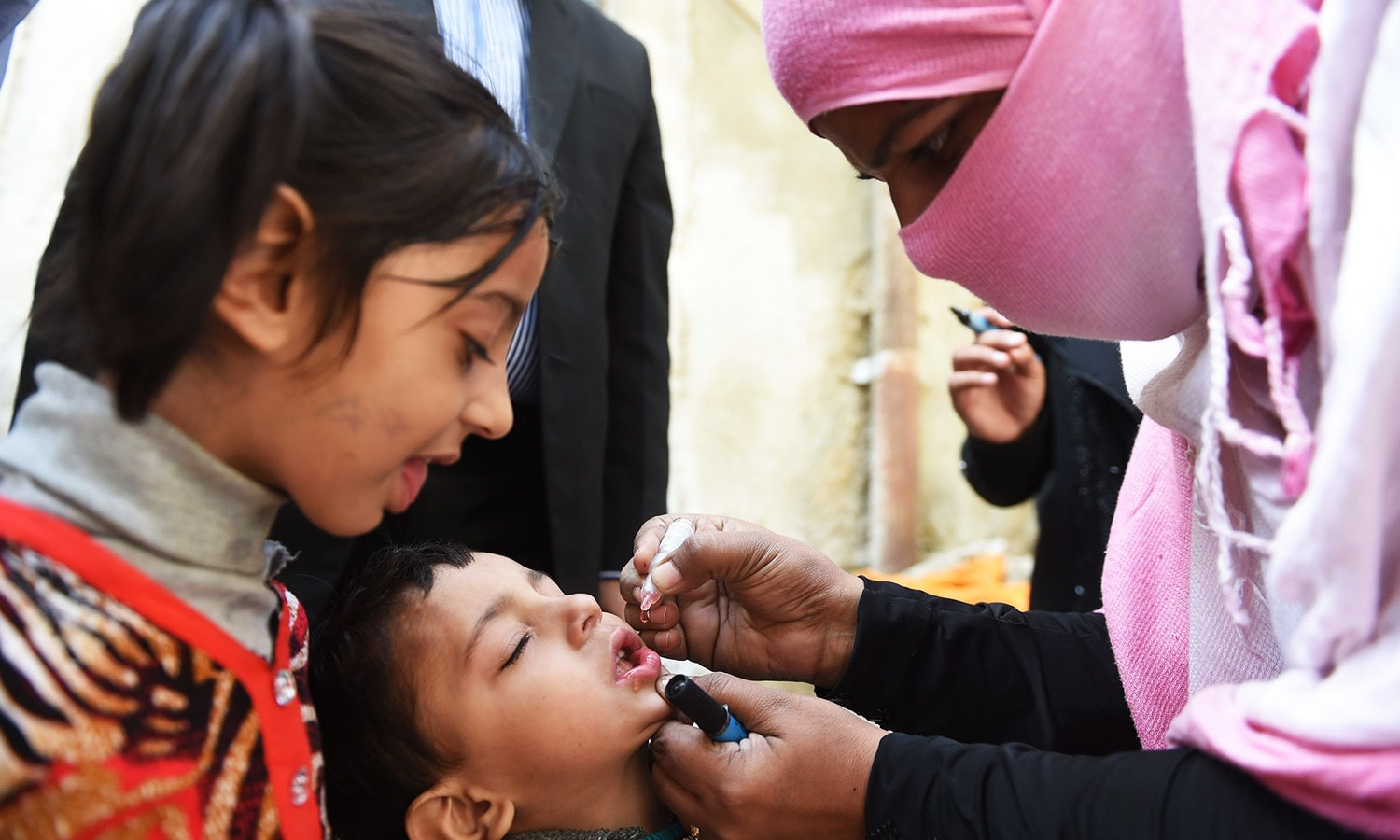 A Pakistani health worker administers polio drops to a child during a polio vaccination campaign in Karachi.—AFP