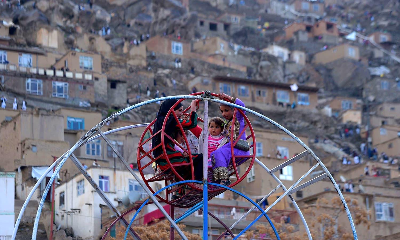 افغان بچے نوروز کے تہوار پر جھولا جھول رہے ہیں۔ بہائی مذہب میں نوروز کے موقع پر بچوں کو عیدی دینے کا رواج ہے — فوٹو اے ایف پی
