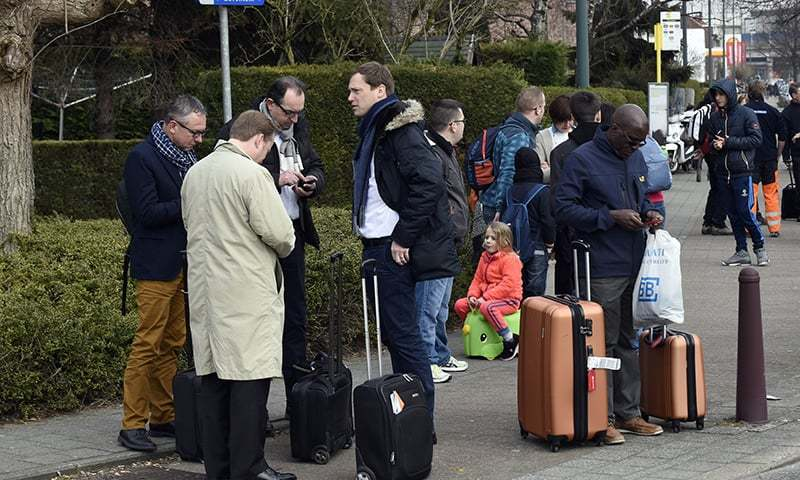 Passengers are gathered near Brussels airport, on March 22, 2016 in Zaventem, following its evacuation after at least 13 people were killed and 35 injured as twin blasts rocked the main terminal of Brussels airport.— AFP