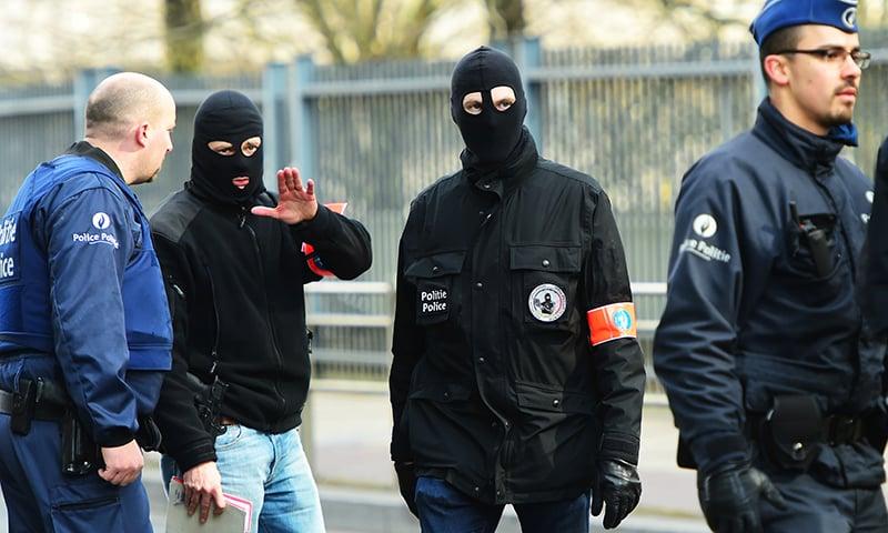 Belgium policemen stand guards at a security perimeter  near Maalbeek metro station. -AFP