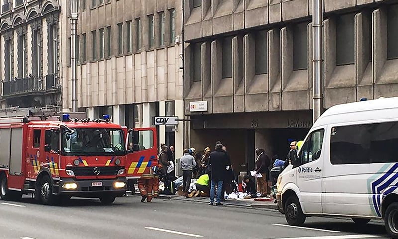 Emergency services take care of wounded people outside the Maalbeek metro station in Brussels. -AFP