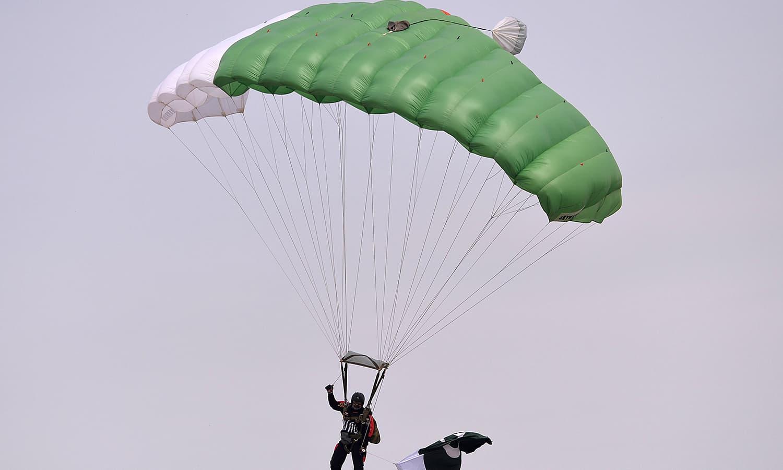 مسلح افواج کے پیرا شوٹرز اور اسکائی ڈائیورز نے قومی پرچم تھامے 10 ہزار فٹ کی بلندی سے چھلانگ لگائی — فوٹو/ اے ایف پی